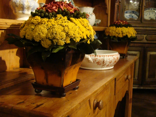 Square brown to gold pot  holding terra cotta rose, pimentina, yarrow and lemon leaf